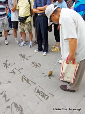 敷石に文字を書くおじいさん